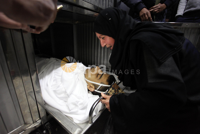 Relatives of Palestinian Mohammed Al-Maqid, 21, who was shot dead by Israeli security forces during clashes at the Israel-Gaza border, mourn over his body at a morgue in hospital in Gaza city, on April 27, 2018. Photo by Mahmoud Ajour