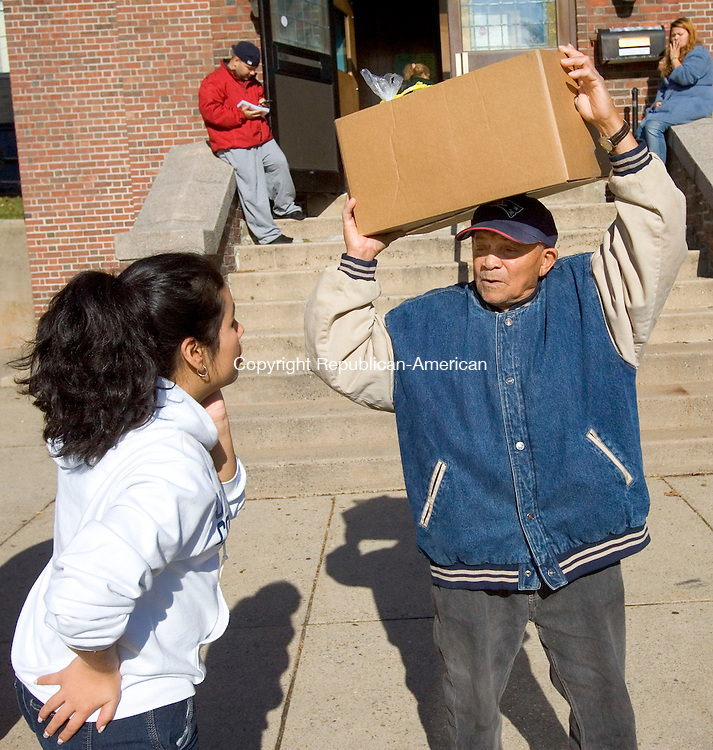 WATERBURY, CT. 21 November 2011-112111SV01--From left, UConn student Hasselth Madrigal of Ansonia helps Luis Pena of Waterbury with his box of groceries at the Greater Waterbury Interfaith Ministries food distribution at the First Lutheran Church in Waterbury Monday.