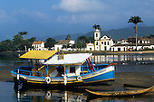 Paraty, Rio de Janeiro State, Brazil; Sol de Verao blue, yellow and white boat with colonial church across the river.