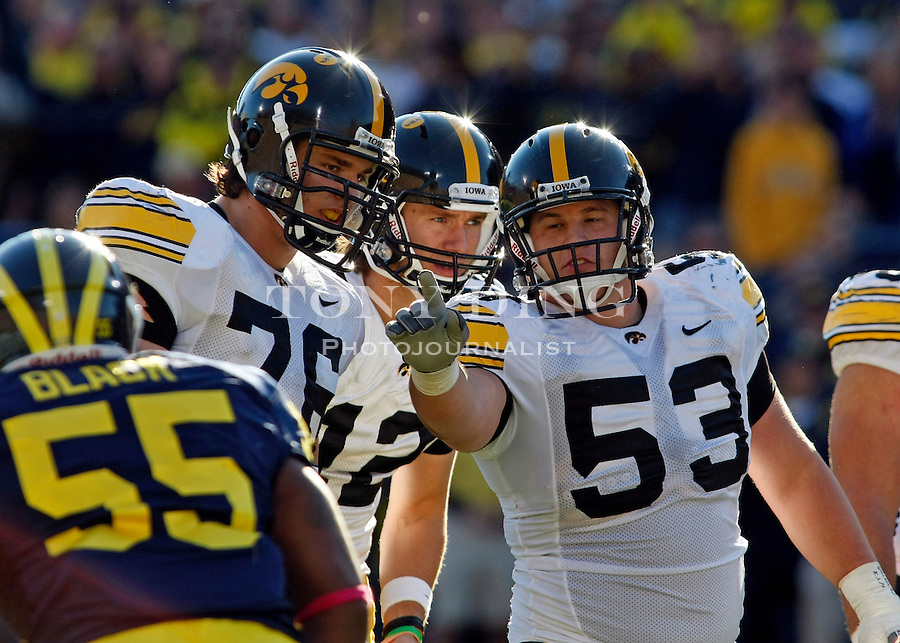 Iowa offensive lineman Nolan MacMillan (76) and quarterback Ricky Stanzi (12) listen to offensive lineman James Ferentz (53) call out Michigan defenders before a down in the second quarter of an NCAA college football game, Saturday, Oct. 16, 2010, in Ann Arbor, Mich. (AP Photo/Tony Ding)