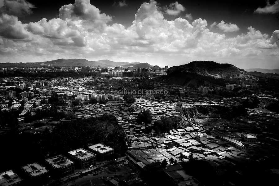 """Mumbai, the city symbolic of the Indian miracle and its sustained economic growth, will become, in 2020, the most populopus metropolis of the world. Today more than 40% of its inhabitants lives in the various slums and shantytowns that define the urban landscape of this Indian """"megacity""""Among the slums, the best known is Dharavi, thanks also to the international success of the Slumdog Millionaire movie. .A view of Mumbai and the Dharavi, may 10 2007."""