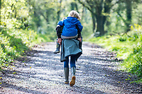 A young boy has a piggy back as they walk through woodland at Canaston Bridge, Pembrokeshire