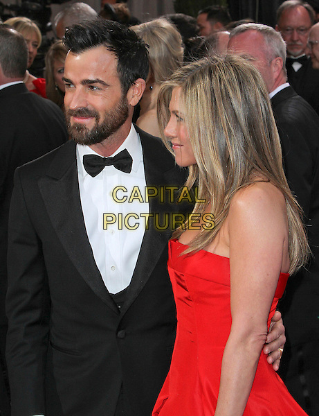 Justin Theroux & Jennifer Aniston (wearing Valentino).85th Annual Academy Awards held at the Dolby Theatre at Hollywood & Highland Center, Hollywood, California, USA..February 24th, 2013.oscars half length black tuxedo white shirt bow tie beard facial hair red strapless dress gown couple engaged side profile .CAP/ADM/SLP/COL.©Colin/StarlitePics/AdMedia/Capital Pictures
