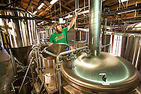 NoDa  Community - NoDa Brewing Company located on Davidson Street in the Charlotte's NoDa Community. Visitors to the brewery can sip on a cold brew while getting an insiders view of the stainless steel brew kettles and fermenters onsite.<br /> <br /> Brian Schonder,  an employee at NoDa Brewing Company , checks the volume in the brewing kettle, at the NoDa company.<br /> <br /> <br /> Charlotte Photographer - PatrickSchneiderPhoto.com