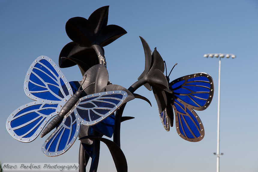 """The butterfly statue at Stanton Central Park, seen in a closeup view taken on a sunny day. The statue is made of blue glass, stainless steel, and black iron, and the stainless steel particularly """"pops"""" in this image."""