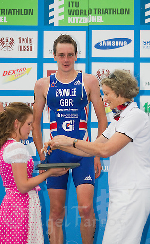 24 JUN 2012 - KITZBUEHEL, AUT - Alistair Brownlee (GBR) of Great Britain waits to be presented with his gold medal by Dr. Sarah Springman CBE, Vice President of the International Triathlon Union (ITU), after winning the elite men's 2012 World Triathlon Series round in Schwarzsee, Kitzbuehel, Austria .(PHOTO (C) 2012 NIGEL FARROW)