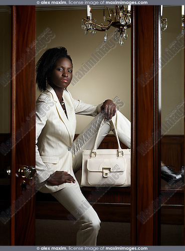 Woman in white suit and with a bag sitting on a table behind partially open doors