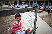 An official keeps the gates open for people arriving to a polling station in Kawhmu township where Aung San Suu Kyi stands as a candidate in parliamentary by-elections April 1, 2012. Myanmar votes on Sunday in its third election in half a century, a crucial test of its nascent reform credentials that could propel opposition leader Aung San Suu Kyi into parliament and convince the West to end sanctions. REUTERS/Damir Sagolj (MYANMAR)