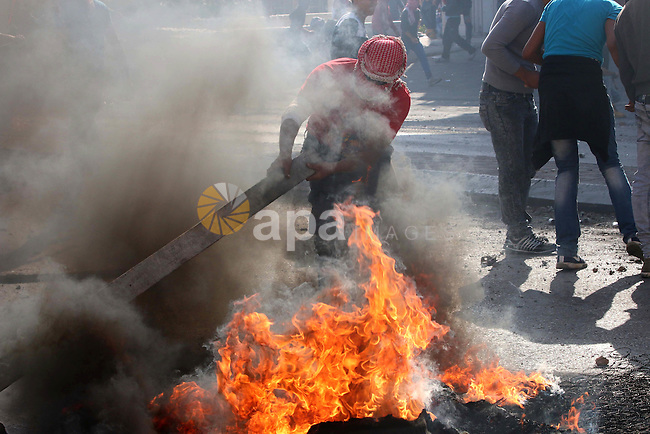 Palestinian protesters burn tires during clashes with Israeli security forces in the West Bank town of Bethlehem on October 9, 2015. Tension and protests rose after an Israeli man on 09 October stabbed four Palestinians in southern Israel, in what is being seen as a revenge attack, officials said. On 08 October several violent incidents happened, including stabbings which left eight Israelis injured, one Palestinian was killed in East Jerusalem and six in the Gaza Strip in clashes with the army while at least six were injured on the West Bank. Photo by Muhesen Amren