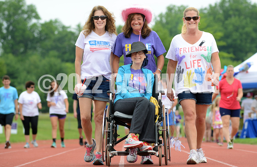 Sheri Katz-Schnur (left) of Newtown, Pennsylvania, Jodi Duffield (center) of Richboro, Pennsylvania, Amy Lepow (right) of Churchville, Pennsylvania and Donna Goodman (seated) of Holland, Pennsylvania walks on the track during Relay for Life, which benefits the American Cancer Society at Council Rock High School South Saturday June 20, 2015 in Richboro, Pennsylvania. (Photo by William Thomas Cain)