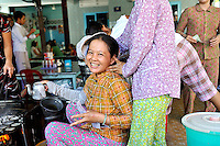 """A woman turns her friend's face towards the camera for a photograph. The women are cooking the ever-popular """"banh khot"""" (a small Vietnamese pancake), specialty of the southern coastal province of Ba Ria-Vung Tau, and especially of Vung Tau City. Vung Tau, Vietnam"""