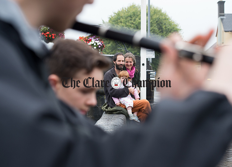 Fia, Saul and Damhnait  Mosbacher watch street musicians during a wet final Sunday of the All-Ireland Fleadh in Ennis. Photograph by John Kelly.