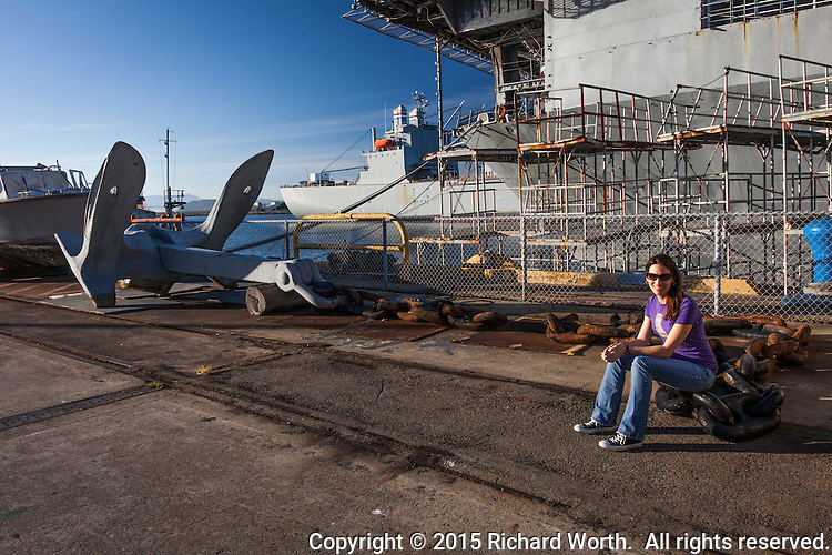 To give perspective, a girl sits on a link in a chain attached to an anchor on the pier next to the USS Hornet at the former Naval Air Station Alameda.