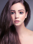 Cute young woman face with big gray eyes and long brown hair retouched in Japanese anime style
