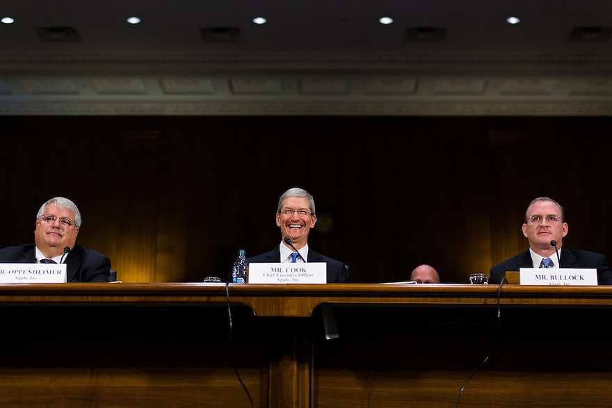 Apple CEO Tim Cook testifies at a Senate homeland security and governmental affairs investigations subcommittee hearing on offshore profit shifting and the U.S. tax code, on Capitol Hill in Washington. Cook defended Apple's tax record during a Senate hearing where lawmakers said the maker of iPads, iPods and Mac computers kept billions of dollars in profits in Irish subsidiaries to avoid U.S. taxes.  He was joined by Apple's Head of Tax Operations Philip Bullock, right,  and CFO Peter Oppenheimer, left.