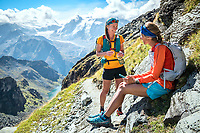 Two women trail runners stopped to eat and check the phone map while running the Via Valais, a multi-day trail running tour connecting Verbier with Zermatt, Switzerland.