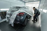 """Switzerland. Canton Geneva. Plan-les-Ouates. Renault Retail Group, RRG Suisse. """"Spot-repair"""" by Dells Angels. Renault Clio car inside a paint booth in auto body repair garage. A worker covers the car with plastic sheet. 4.03.2020 © 2020 Didier Ruef"""