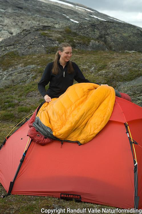 Jente legger sovepose til tørk og lufting på telt. ---- Girl drying sleaping bag outside tent.