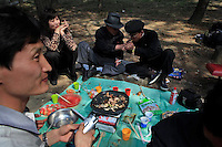 "A North Korean man lights the cigarette for another during a picnic in Pyongyang, North Korea, Wednesday, April 18, 2012. ""Inside DPRK"""