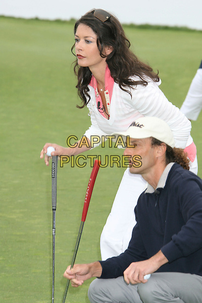 CATHERINE ZETA-JONES & KENNY G.9th Annual Michael Douglas & Friends Celebrity Golf Event.held at the Trump National Golf Club, Rancho Palos Verdes, California, USA. .April 29th, 2007.sport full length white pink striped stripes top cropped beige trousers beige club bending crouching blue baseball cap hat .CAP/ADM/RE.©Russ Elliot/AdMedia/Capital Pictures