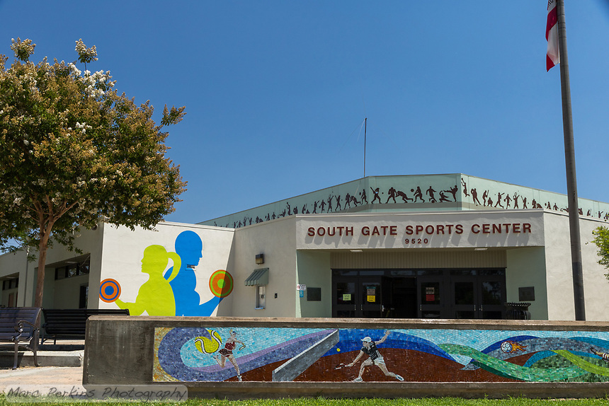 The South Gate Sports Center, seen head-on on a cloudless sunny day.   The sports-themed tile mosaics, flowering trees, lighting, and painted monochromatic silhouettes of athletes are all visible.