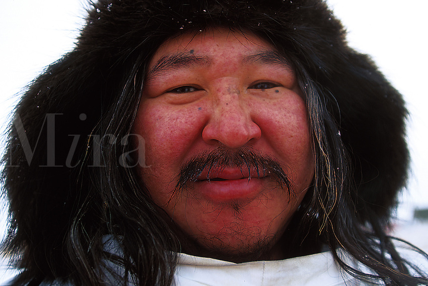 Portrait of a smiling male Native Alaskan ina fur hat with ear flaps. Alaska.