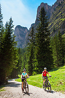 Italy, South Tyrol (Trentino - Alto Adige), Dolomites, near Selva di Val Gardena: Valley Langental (Vallunga) in Puez-Geisler Nature Park, mountainbiker with towers of Monte Stevia at background | Italien, Suedtirol (Trentino - Alto Adige), Dolomiten, bei Wolkenstein in Groeden: das Langental (Vallunga) im Naturpark Puez-Geisler, Mountainbiker vor den Tuermen der Stevia