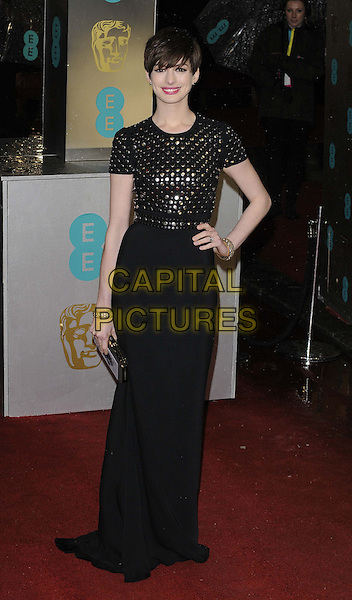Anne Hathaway.EE British Academy Film Awards at The Royal Opera House, London, England 10th February 2013.BAFTA BAFTAS arrivals full length silver circles top skirt clutch bag bracelet black dress white hand on hip.CAP/CAN.©Can Nguyen/Capital Pictures.