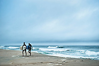 Two surfers walk along the beach, Nauset Beach, Cape Cod, MA, USA