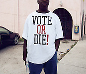 Opa-Locka, Miami-Dade County, Florida.USA.November 2, 2004.Voters line up with observers and lawyers from both sides watching over the voters and pollsters...A voters wears the tee shirt with the rapers P.Diddy sloggen.