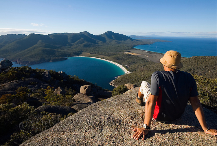 A man looks out over Wineglass Bay from the summit of Mt Amos.  Freycinet National Park, Tasmania, AUSTRALIA