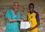 Dr. Tom Catena (left), a Catholic lay missionary from the United States, awards Lakuwa Lokolo Rama his diploma as a registered nurse, during a ceremony at the Mother of Mercy Hospital in Gidel, a village in the Nuba Mountains of Sudan.<br /> <br /> Rama studied for the diploma at the Catholic Health Training Institute in Wau, South Sudan, but after graduation returned home to his native Nuba Mountains. <br /> The area is controlled by the Sudan People's Liberation Movement-North, and frequently attacked by the military of Sudan. The Catholic hospital is the only referral hospital in the war-torn area.