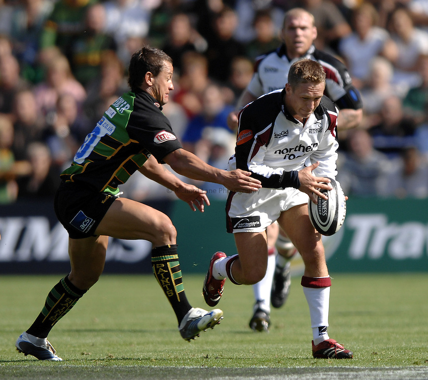 Photo: Richard Lane..Northampton Saints v Newcastle Falcons. Guinness Premiership. 03/09/2006. .Falcons' Jonny Wilkinson breaks past Carlos Spencer.
