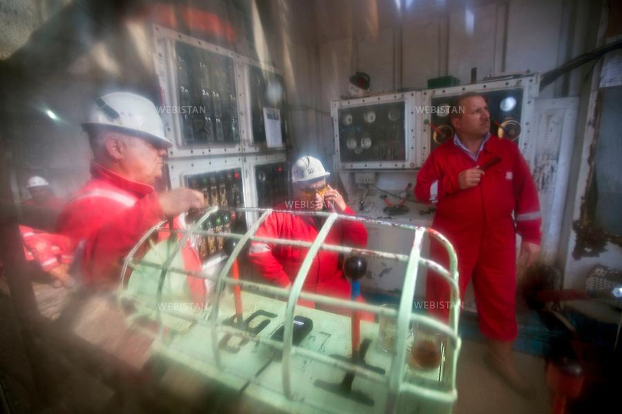 Azerbaijan, Baku, Caspian Sea, Neft Dashlari (Oil Rocks), SOCAR Platform, April 20, 2012<br /> Workers on a platform belonging to the State Oil Company of the Azerbaijan Republic (SOCAR) watch oil drilling from inside a control center within the Neft Dashlari (Oil Rocks) settlement. The settlement was built in 1949 and was the first offshore oil platform in the world. Oil Rocks, called a &ldquo;city in the sea,&rdquo; is actually a functioning town with a population of about 2,000 people as well as roads and restaurants. Today, the site is operated by SOCAR and continues to produce oil and gas.<br /> <br /> Azerba&iuml;djan, Bakou, mer Caspienne, Neft Dachlari (&laquo; Roches huileuses &raquo;), plateforme SOCAR, 20 avril 2012<br /> Des ouvriers de la plateforme d&rsquo;une compagnie p&eacute;troli&egrave;re nationale de la R&eacute;publique de l&rsquo;Azerba&iuml;djan (SOCAR) regardent un forage p&eacute;trolier de l&rsquo;int&eacute;rieur d&rsquo;un centre de contr&ocirc;le de l&rsquo;&eacute;tablissement de Neft Dachlari (&laquo; Roches huileuse &raquo;). Cet &eacute;tablissement construit en 1949 est la premi&egrave;re plateforme p&eacute;troli&egrave;re du monde. Neft Dachlari, appel&eacute;e la &laquo; ville dans la mer &raquo;, est une ville fonctionnelle d&rsquo;environ 2 000 habitants munie de routes et de restaurants. Aujourd&rsquo;hui, le site est exploit&eacute; par SOCAR et continue de produire du p&eacute;trole et du gaz.