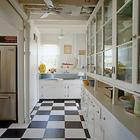 The whitewashed kitchen has a traditional look emphasised by the black and white tiled floor.