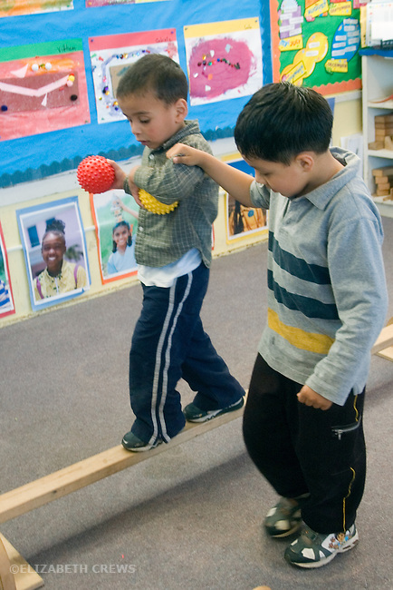 Berkeley CA Preschool student giving classmate balancing support while practicing on balance beam.