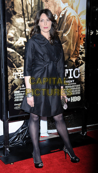 "MICHELLE FORBES.The Los Angeles premiere of HBO's new miniseries event ""The Pacific"" at Grauman's Chinese Theatre in Hollywood, California.  .February 24th, 2010.full length black dress tights shoes open toe clutch bag coat belted belt platform bracelet .CAP/ROT.©Lee Roth/Capital Pictures"