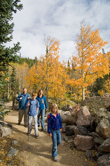 Family hiking on trail through the golden colors of autumn in aspen stands above Bear Lake on a September morning in Rocky Mountain NP, Colorado