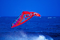 A windsurfer with a vivid red sailboard takes a back flip off a wave at Hookipa Beach park, Maui