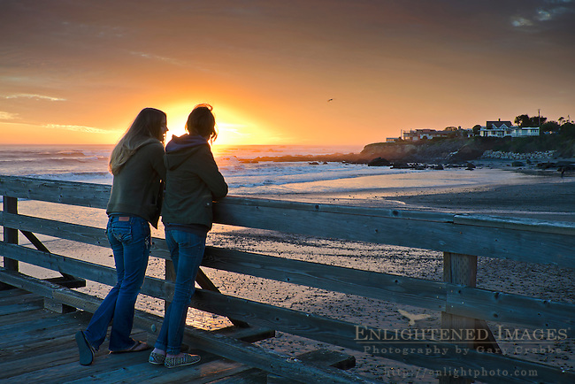 Two young women friends watch the sunset from the Cayucos Pier, Cayucos, San Luis Obisbo County, California
