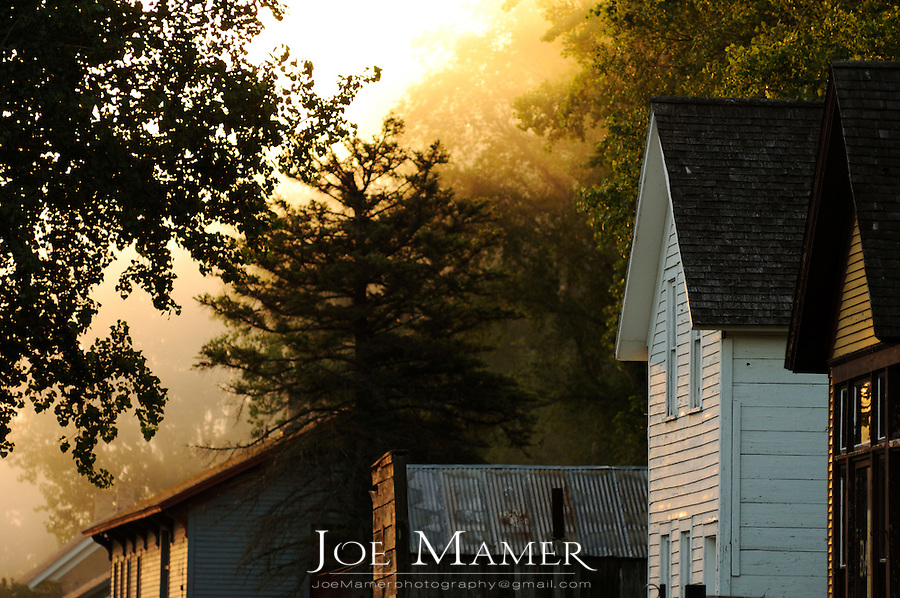 Main street sunrise on a foggy morning at Murphy's Landing historical site in Shakopee, Minnesota. Murphy's Landing is a collection of old buildings from the local area where period reenactment teaches visitors about life in the last century.
