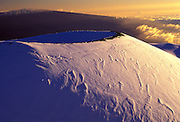 The summit of Mauna Kea crater covered with snow with a golden sky in the background.