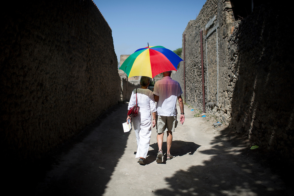 A couple uses an umbrella to shield themselves from the sunlight as they make their way through the Pompeii ruins on Friday, Sept. 18, 2015. The city of Pompeii was destroyed when nearby Mount Vesuvius erupted on August 24, AD 79. The town and its residents were buried and forgotten until the ruins were discovered and eventually excavated hundreds of years later. The ruins are one of Italy's top tourist attractions today. (Photo by James Brosher)