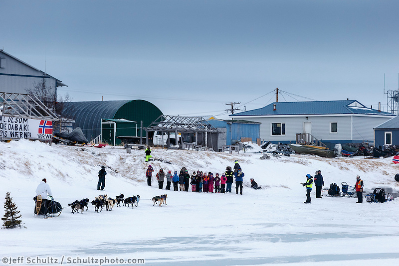 A crowd of 2nd graders and others are on hand to greet Martin Buser as he arrives at the Unalakleet checkpoint in the morning on Monday March 16, 2015 during Iditarod 2015.  <br /> <br /> (C) Jeff Schultz/SchultzPhoto.com - ALL RIGHTS RESERVED<br />  DUPLICATION  PROHIBITED  WITHOUT  PERMISSION