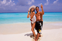 Fun Hispanic couple using their cell phone camera on the beaches of Cancun Mexico