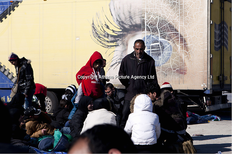 Pictured: Migrants resting against an advertising board Monday 22 February 2016<br /> Re: Thousands of migrants, most from Syria, have landed to the port of Pireaus, after crossing the border from Turkey to various islands like Lesvos and Kos in Greece.