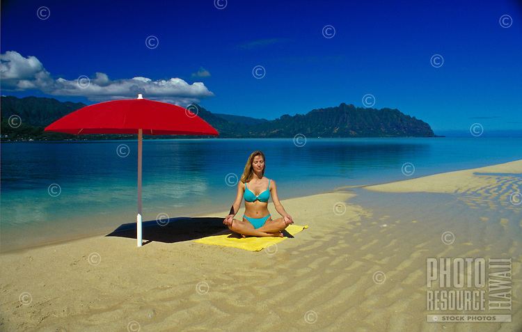 Woman meditating at Ahu O Laka, Kaneohe sand bar, Oahu