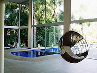 The 82 ft swimming pool extends into the large living room where a woven chair hangs from the double-height ceiling