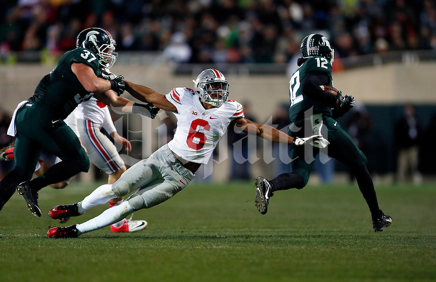 Ohio State Buckeyes wide receiver Evan Spencer (6) gets held by Michigan State Spartans fullback Trevon Pendleton (37) as he tries to tackle Michigan State Spartans wide receiver R.J. Shelton (12) during the fourth quarter of the NCAA football game at Spartan Stadium in East Lansing, Michigan on Nov. 8, 2014. (Adam Cairns / The Columbus Dispatch)