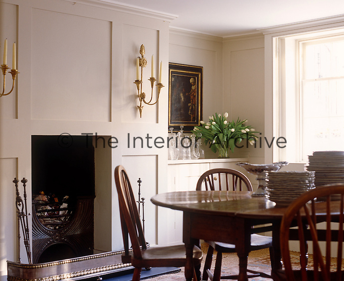 This traditional style dining room has cream-painted panellling and antique dining table and chairs